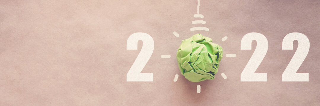 2022 with Green paper light bulb, New year eco CSR goal and sustainable living resolution concept