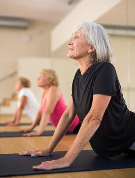 Senior women practicing cobra pose during group yoga training.