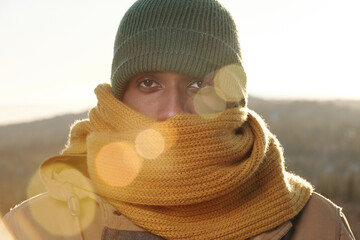 Fototapeta Frozen young man of African ethnicity in knitted scarf and cap looking at camera obraz