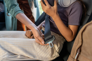 Obraz Hand of young mother fastening her daughter with seatbelt before driving to school - fototapety do salonu