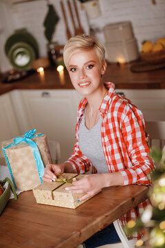 A beautiful girl in a red plaid shirt sits at the kitchen table with Christmas gifts on Christmas and New Year's Eve. Happy and joyful emotions. Christmas celebration.