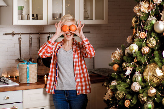 A beautiful girl in a red plaid shirt and blue jeans stands near the Christmas tree and covers her eyes with two tangerines. Happy and joyful emotions. Christmas celebration.