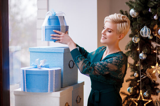 A beautiful girl in a green dress stands with Christmas gifts by the window on the eve of Christmas and New Year. Girl decorate living room for Christmas.