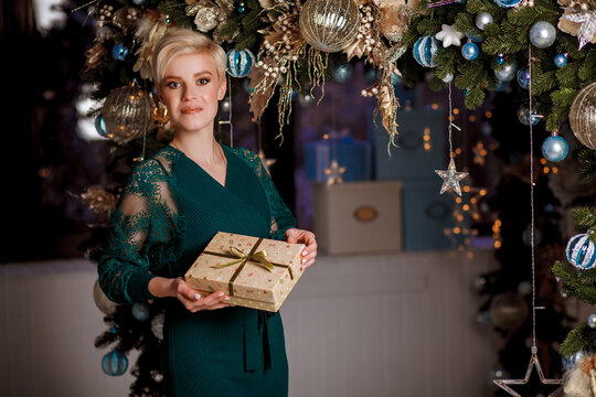 Beautiful girl in a green dress with a gift in hands on Christmas and New Year's Eve. Portrait smilling girl near Xmas tree. Christmas celebration. Girl decorate living room for Christmas.