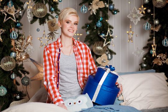 Beautiful girl in a red plaid shirt sits with gifts on Christmas and New Year's Eve. Merry Christmas and Happy New Year. Happy and joyful emotions. Christmas celebration.