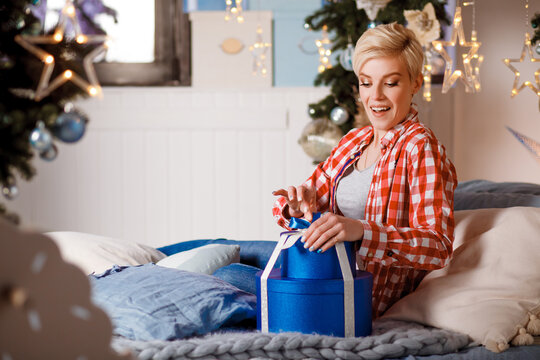 Beautiful girl in a red plaid shirt opens presents on Christmas and New Years Eve. Merry Christmas and Happy New Year. Happy and joyful emotions. Christmas celebration.