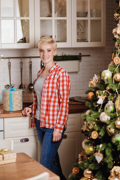 Portrait of a beautiful girl in a red plaid shirt and blue jeans who stands in the dining room with a gift near the New Year tree. Happy and joyful emotions.