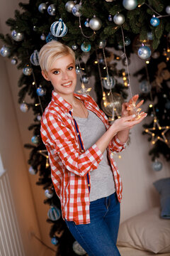 A beautiful girl in a red plaid shirt decorates her room with Christmas toys. Merry Christmas and Happy New Year. Happy and joyful emotions. Christmas celebration.