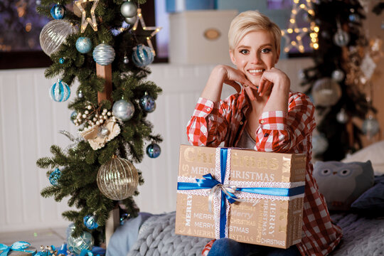 Beautiful girl in a red plaid shirt sits with Christmas gifts on Christmas and New Year's Eve. Merry Christmas and Happy New Year. Happy and joyful emotions.
