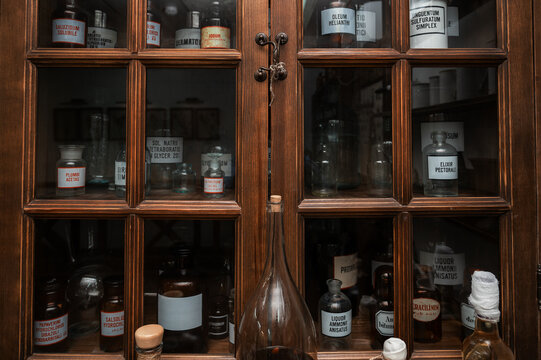 Empty scent bottles in old pharmacy. Wooden antique cupboard for medical drug storage