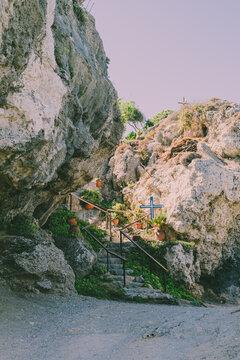 Greece Island Beach View on Monastery, ladder and Cross among rocks.