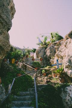 Greece Island Beach View on Monastery, ladder and Cross among rocks, plants and greens.