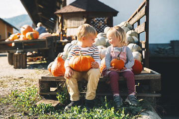 Obraz Family with kids at fall season. Preschool children sitting in pile of pumpkins at local farm market and picking pumpkin on Halloween or Thanksgiving holiday. - fototapety do salonu