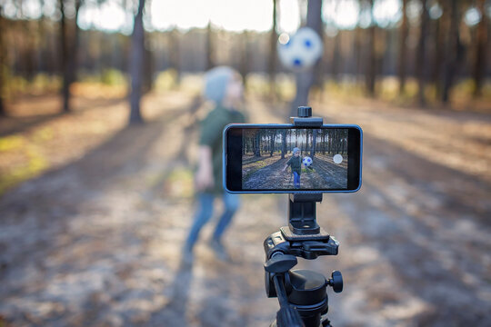 Little boy, young football player, hitting the ball and recording viral video film with smartphone to share in social media in autumn forest, sport blogger, outdoor lifestyle, healthy active life