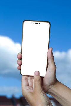 Smartphone mockup with blank white screen for text but against blue sky background