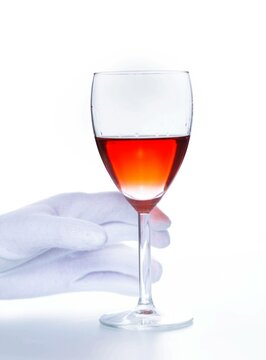 Sommelier's hand in a white glove takes a glass of red wine on a white background
