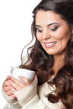 Portrait of beautiful curly woman wearing warm clothing holding cup isolated