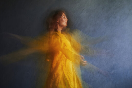 Mature woman in yellow dress dancing by gray wall