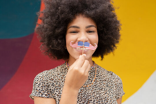 Afro woman holding mustache prop in front of wall