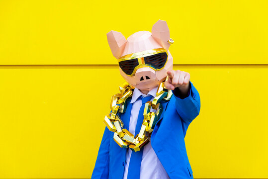Man wearing vibrant blue suit, pig mask and large golden chain pointing toward camera