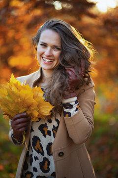happy young woman in beige coat and orange hat