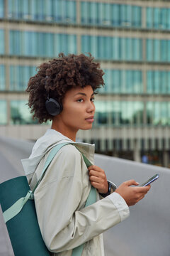 Sideways shot of thoughtful African American woman holds mobile phone checks email box downloads song to playlist poses with rolled karemat against blurred city background has regular training