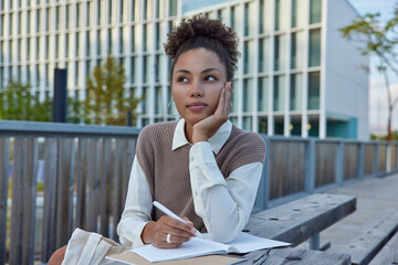 Fototapeta Thoughtful female student writes notes in notebook holds pen has pensive expression puts down her thoughts in personal diary during leisure time wears neat clothes makes schedule records checklist obraz
