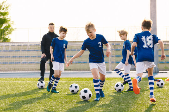 Group of Friends Training Football with Young Coach. School Boys Kicking Balls on Grass Field. Young Footballers Improving Soccer Skills on Practice Session