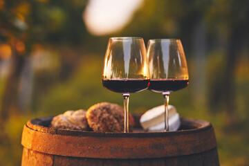 Fototapeta Two glasses full of red wine on an old barrel in the vineyard obraz