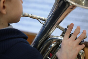Boy child playing a musical instrument silver trumpet background for music theme close-up