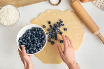 Fototapeta Woman cooking blueberry galette on light table obraz