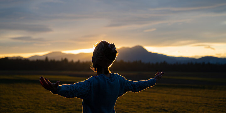 Young woman meditating in nature at sunset