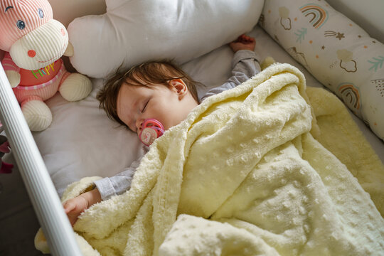 Small infant baby girl lying in cradle bed at home in day sleeping - childhood parenthood and growing up concept