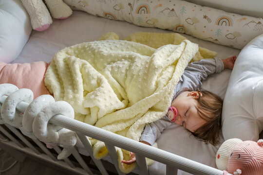 Top view on small infant baby girl lying in cradle bed at home in day sleeping - childhood parenthood and growing up concept