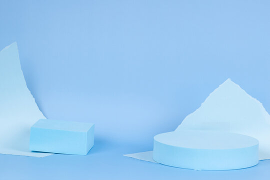 Abstract monochrome composition with empty round podium platform for product presentation and torn paper edges on light blue background. Front view