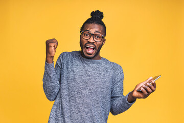 Fototapeta Photo of overjoyed happy black african american man knowing that he became winner of something so rejoicing enjoying news information while isolated over yellow background. obraz