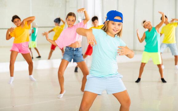 Group of active children dancing hip-hop dance in studio.