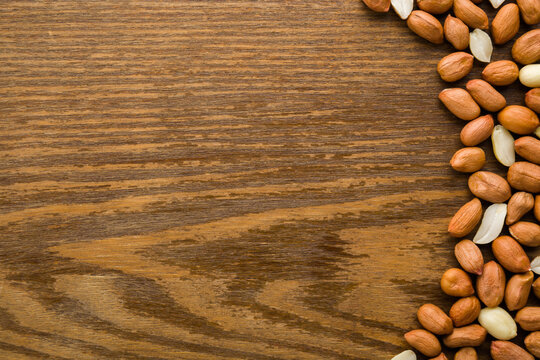 Brown almond nuts on dark wooden table background. Closeup. Empty place for text. Top down view.