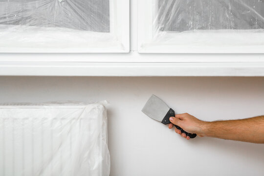 Young adult man hand using spatula and plastering wall with white fresh finishing putty at radiator under windowsill. Closeup. Repair work of home. Top down view.