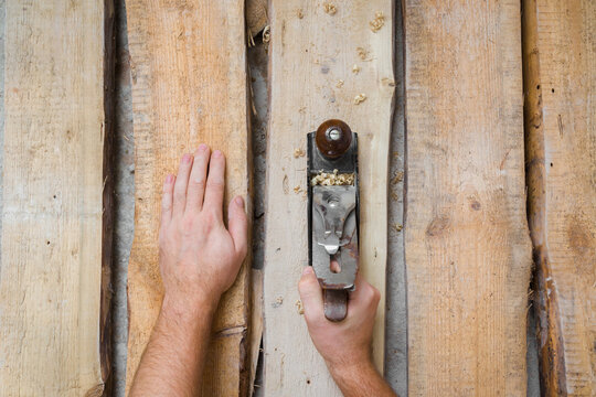 Young adult man hands using jointer and shaving old wooden floor planks. Closeup. Preparing for repair work of home. Flooring restoration. Top down view.