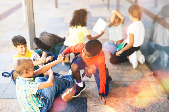 Carefree tweenagers students friendly talking and having fun near school building in warm autumn day.