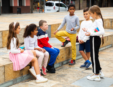 Cheerful multiethnic group of tweens spending time together on city street in warm fall day .