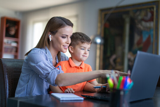 Happy young mother showing something to son on laptop in home office