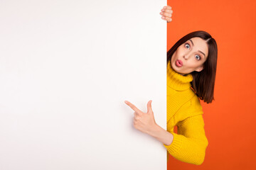 Photo of young woman amazed shocked indicate finger empty space white wall information ads isolated...