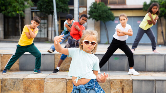Portrait of emotional girl doing hip hop movements during open air group dance class