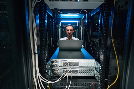 Male network administrator running software check of server equioment