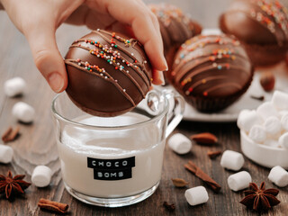 Fototapeta Chocolate cocoa bomb in hand near glass cup with plant-based milk and choco bomb text. Ball made from milk chocolate with marshmallow. Stylish orange toned image of trendy winter hot chocolate drink obraz