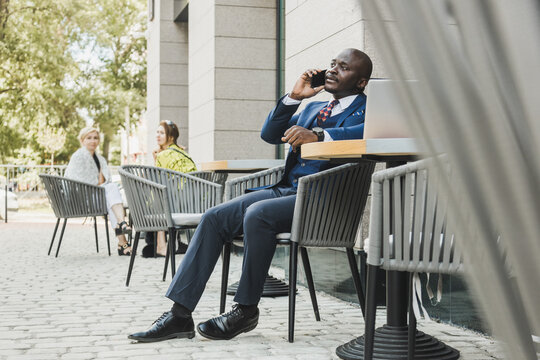 Portrait of a black African American businessman in a suit sitting in a city cafe outdoors and talking on the phone.