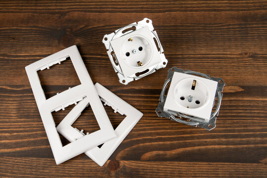 Electrical socket with decorative plastic parts on a wooden background