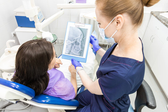 Dentistry concept. Professional dental services and modern equipment without pain. The doctor consults and treats the young woman